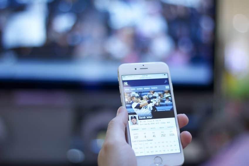 Imagem mostra pessoa segurando um celular na frente. Ao fundo, embaçada, está uma televisão.
