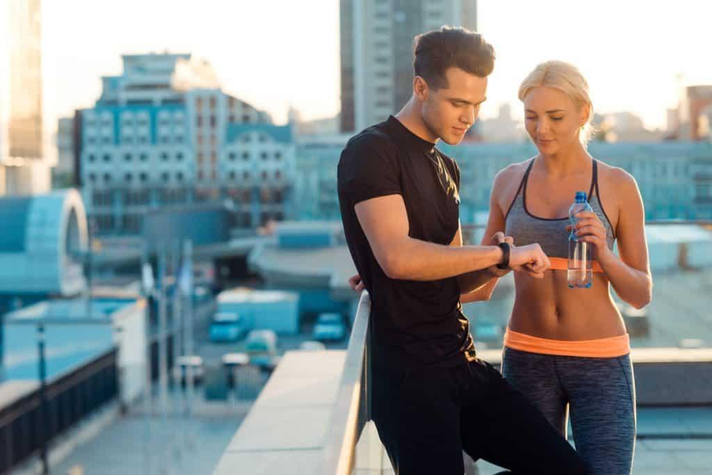 Imagem de um rapaz mostrando sua smartband para uma garota.