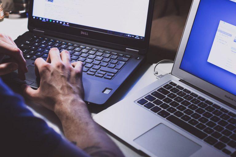 Homem digitando em notebook da Dell.
