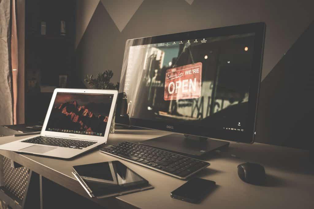 Imagem mostra uma mesa de trabalho com um notebook, um computador, um tablet, um celular e um teclado e mouse sem fio.