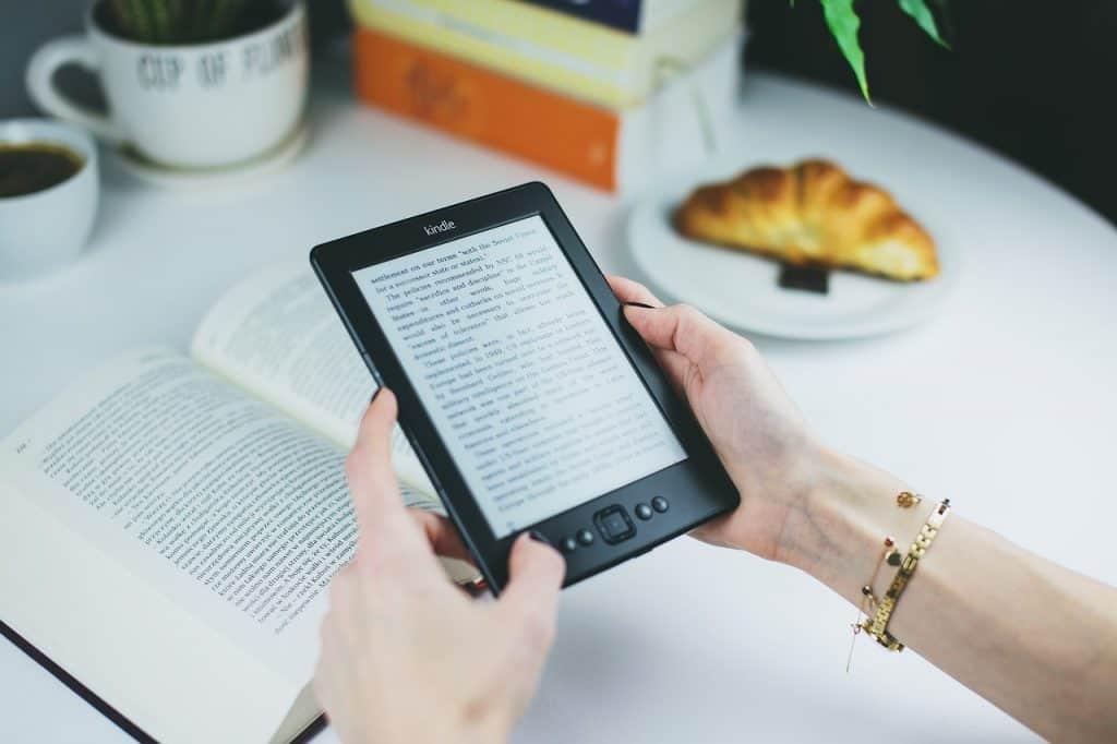 Na foto uma mulher segurando um Kindle em cima de uma mesa com um livro, um croissant e algumas canecas.