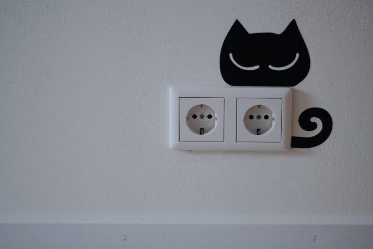 Na foto duas tomadas com um adesivo de gato na parede.