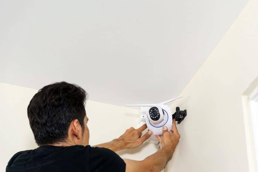 Homem instalando câmera de segurança em área interna.