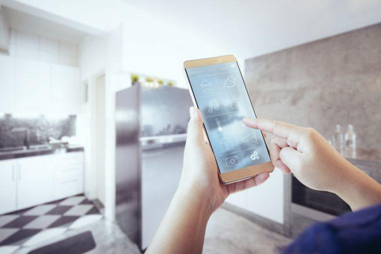 Imagem de pessoa utilizando o celular para controlar suas tomadas inteligentes