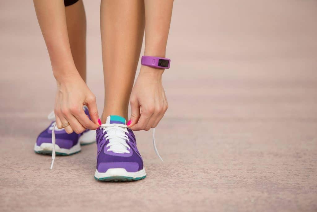Imagem de uma garota amarrando seu tênis.