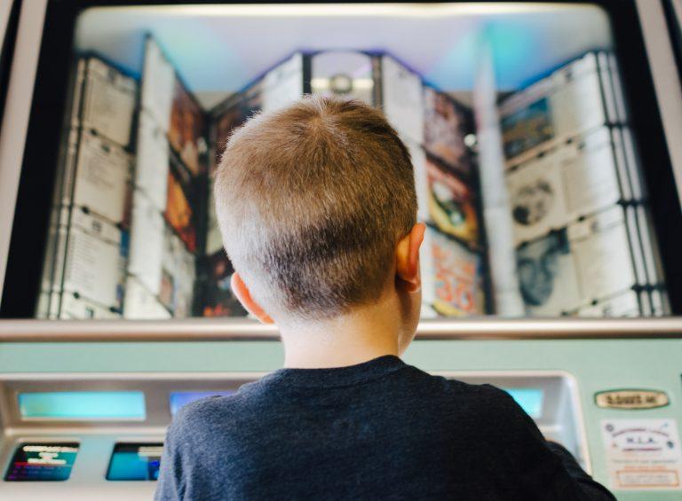 Imagem de um menino escolhendo uma música para tocar em uma jukebox.