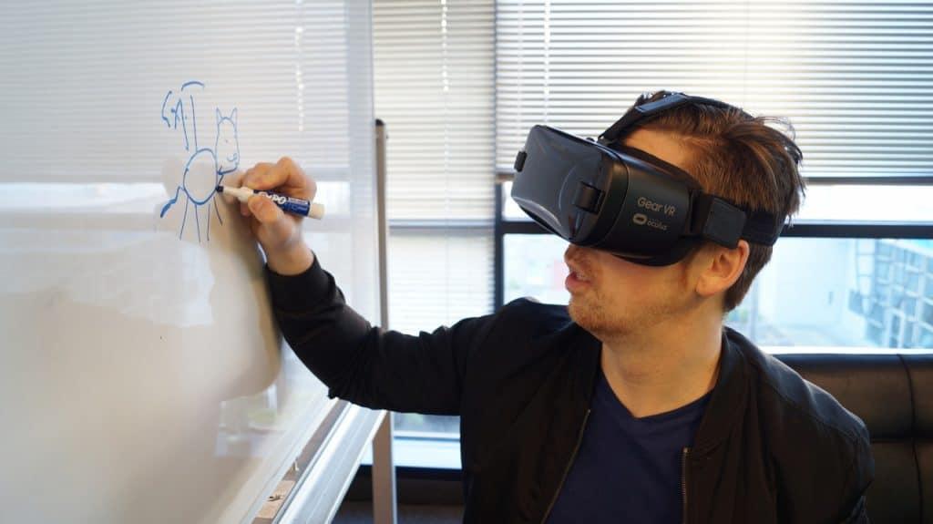Homem usando óculos de realidade virtual desenhando em um quadro branco.