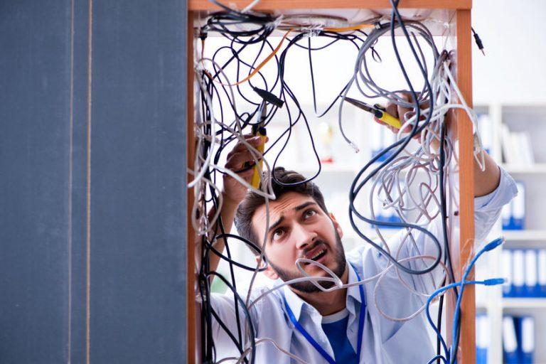 Rapaz luta com emaranhado de cabos de computador