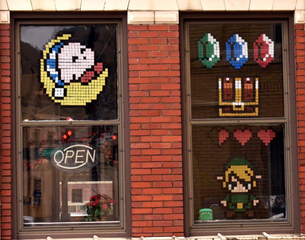 Imagem mostra a fachada de uma loja com pequenos mosaicos de papel colorido colados na janela. Eles são temáticos de jogos da Nintendo.