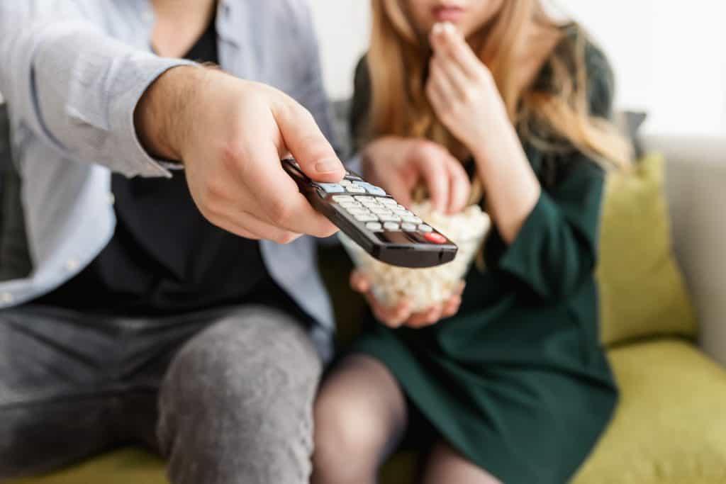 Na imagem está um homem a esquerda e uma mulher a direita sentados em um sofá. A mulher está comendo pipoca e o homem segurando um controle remoto de televisão.