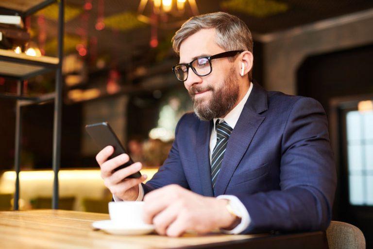 Homem sentado em cafeteria tomando uma xícara de café, mexendo no celular e usando AirPods.