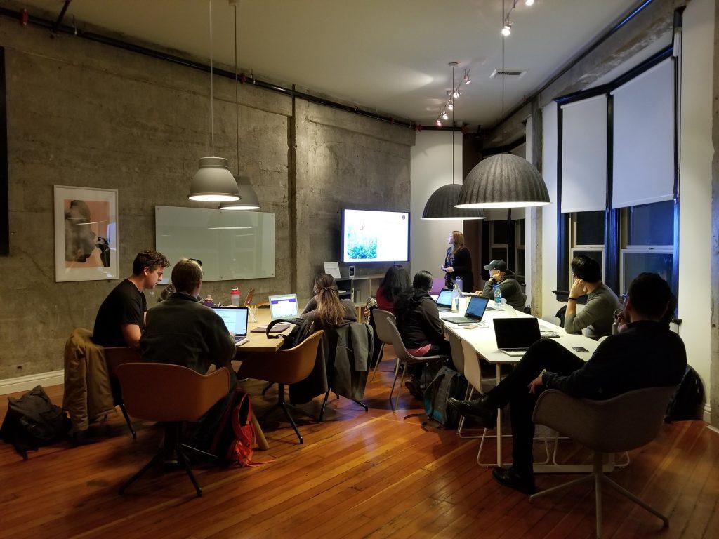 Pessoas sentadas na mesa com notebooks e assistindo TV.