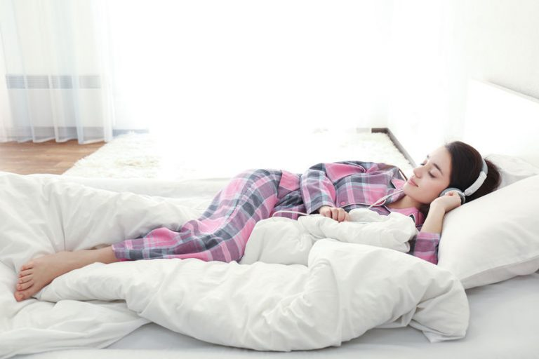 Garota dormindo em cama com roupa de cama branca, vestindo pijama xadrez e usando fone de ouvido.