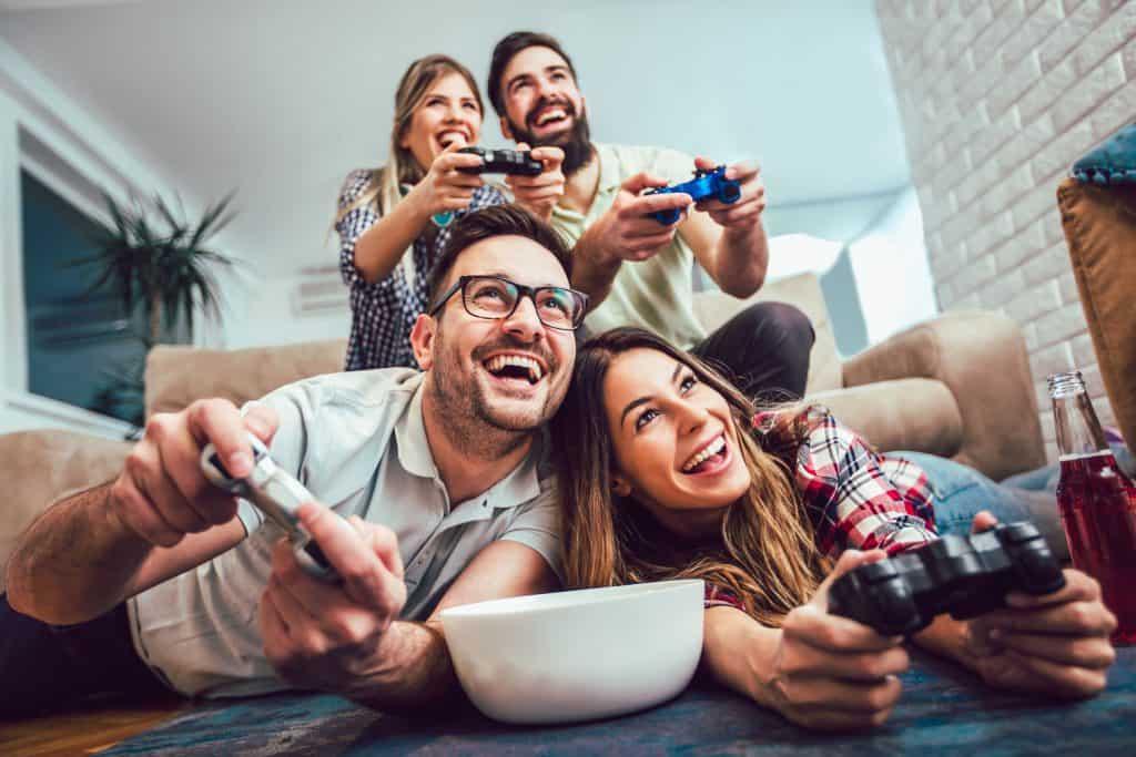 Na foto dois casais jogando videogame dentro de uma sala de estar.