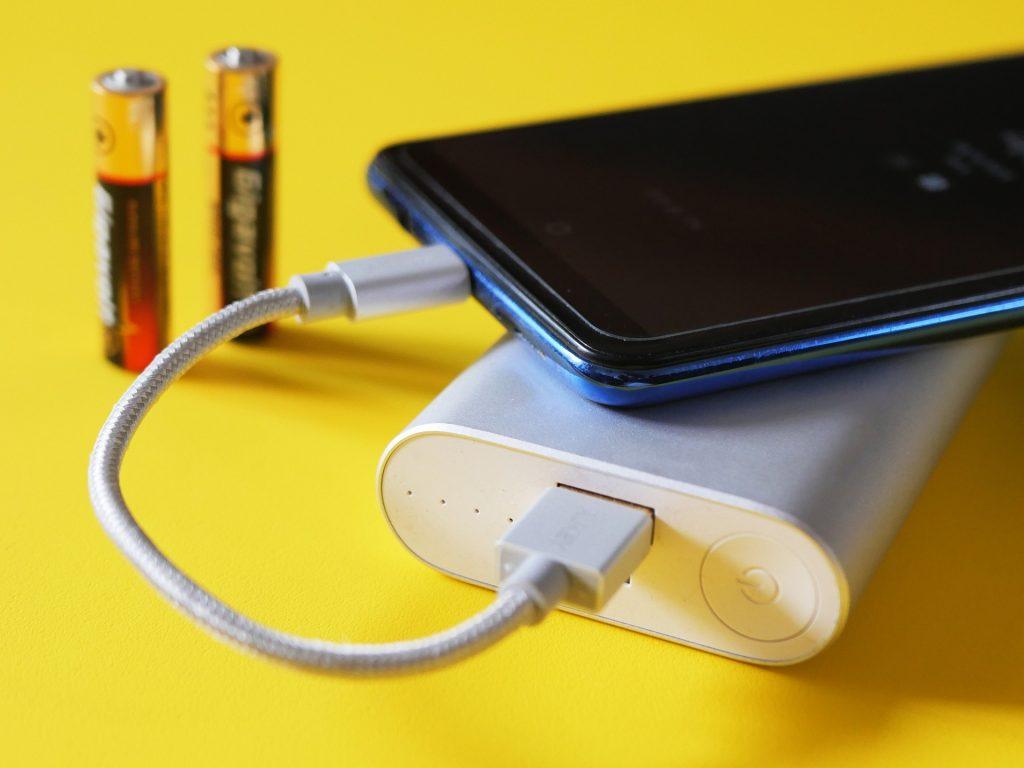 Imagem mostra uma composição com um celular, um power bank e duas pilhas sobre uma superfície amarela. O foco seletivo está na porta USB do power bank, de onde sai um cabo que conecta-se ao celular.