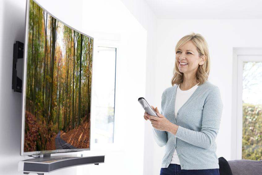 Mulher com controle em frente a uma TV tela curva.