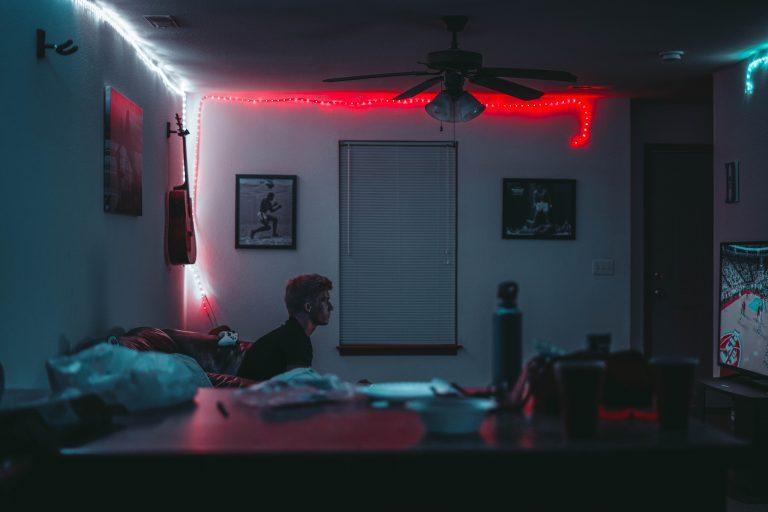 Imagem mostra um quarto e um menino sentado no sofá jogando videogame