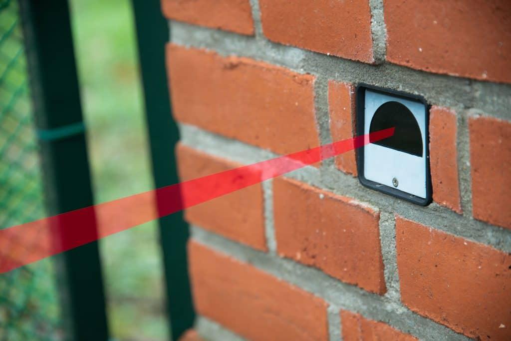 Imagem mostra um sensor de barreira instalado em parede de tijolinhos.