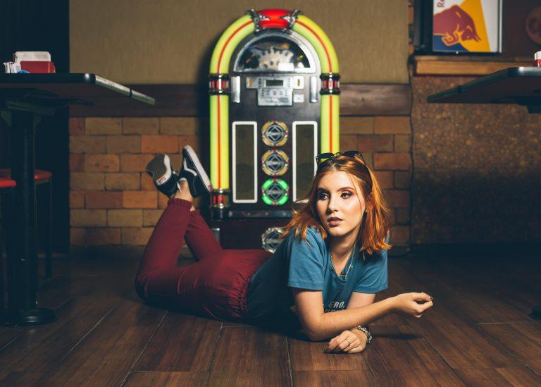 Imagem de uma garota posando em frente a uma jukebox.