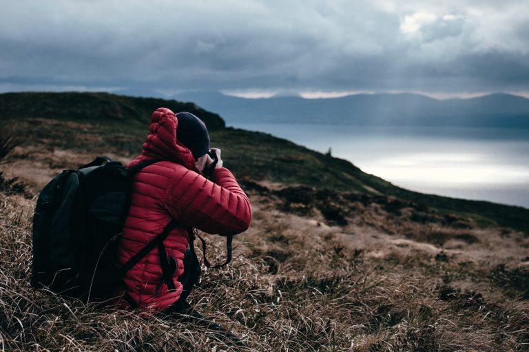 Foto de um homem de casaco de frio vermelho, touca preta e mochila para fotografia, em meio a uma mata, fotografando o horizonte. Ao fundo, o que parece ser um lago ou um rio.