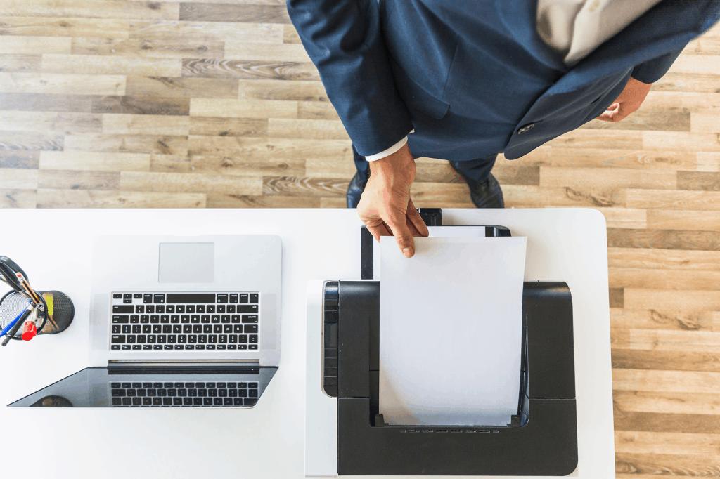 Visão aérea de homem negócios levando papel a um scanner em mesa de escritório.