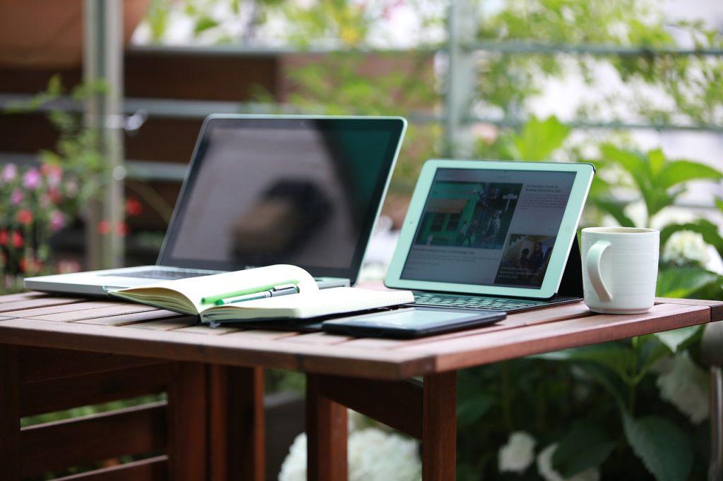 Imagem de notebook e tablet com teclado sobre mesa.
