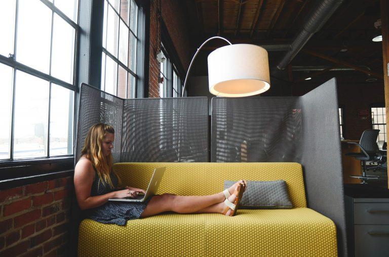 Mulher usando notebook no sofá.