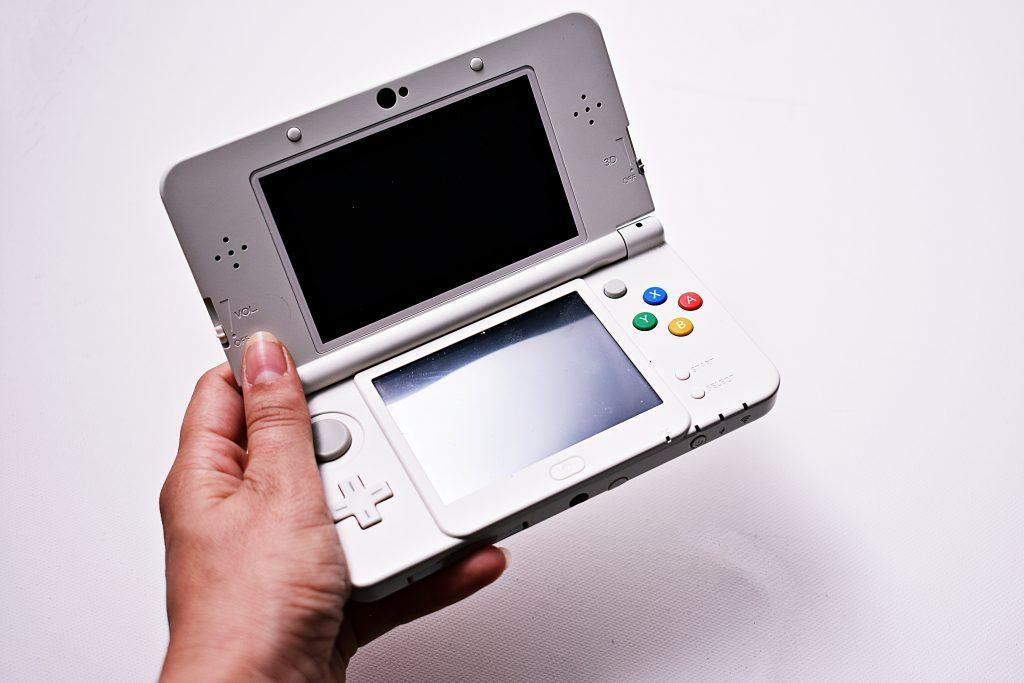 Imagem mostra uma mão segurando um New Nintendo 3DS XL, sob um fundo branco.