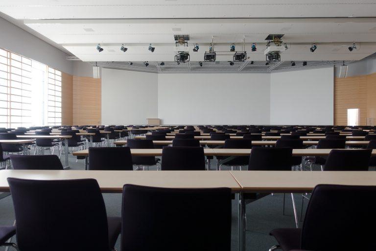 Imagem de sala de reunião com uma grande tela de projeção