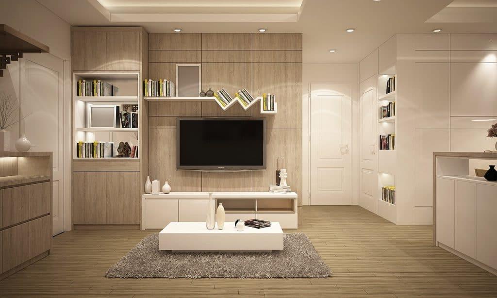 Na foto uma sala de estar com móveis em madeira clara, uma mesa de centro branca e uma televisão na parede.