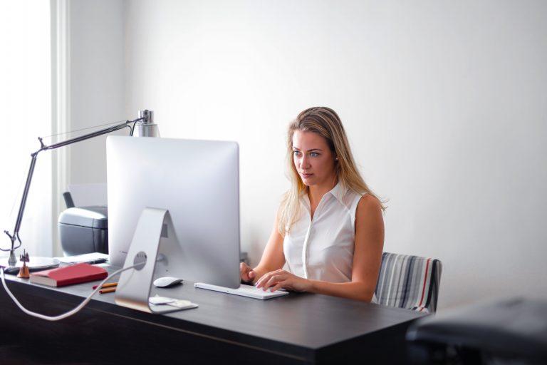 Imagem de uma mulher utilizando um computador All in One.