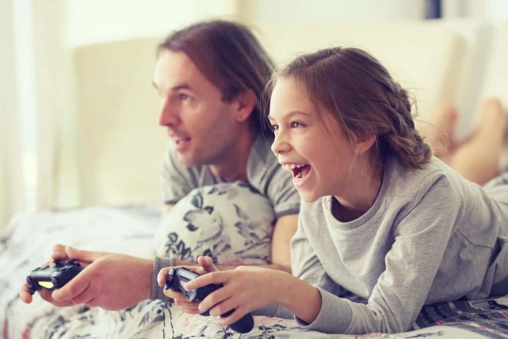 Imagem mostra pai e filha deitados de bruço jogando videogame e rindo.