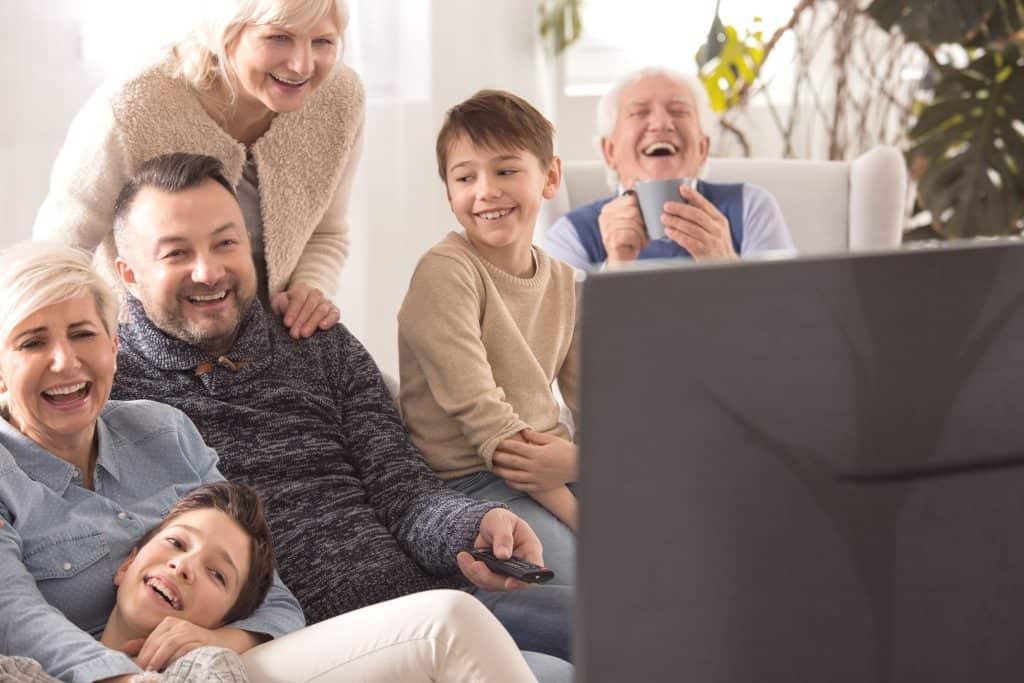Na foto um grupo de pessoas assistindo TV em uma sala de estar sorrindo.