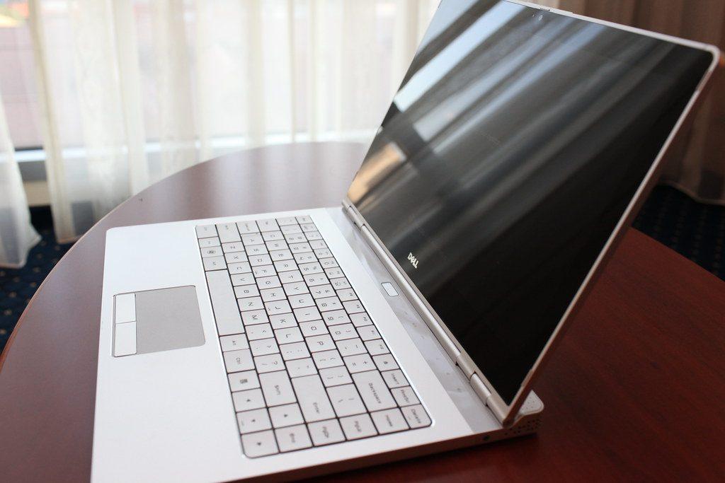 Notebook Dell prateado visto na lateral. Ele está em cima de uma mesa de madeira e ao fundo há um pedaço de janela com cortina transparente.