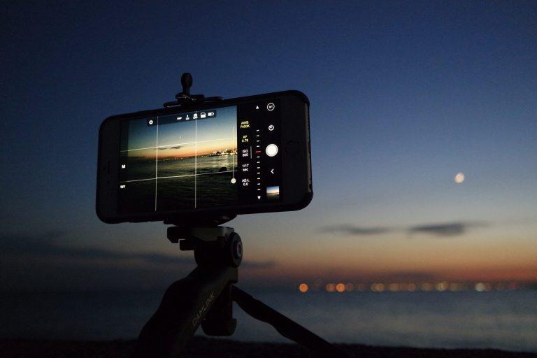 Imagem de um celular encaixado em um tripé.