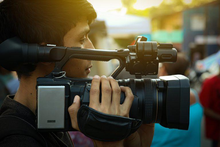 Rapaz segurando filmadora no ombro.