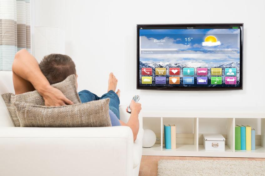 Homem deitado no sofá assistindo à TV.