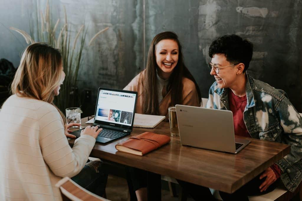 Três pessoas sentadas em uma mesa, cada uma com um notebook Samsung.