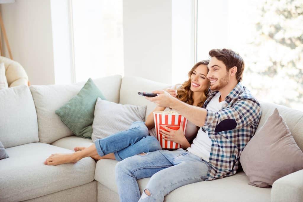 Imagem de um casal assistindo um filme na TV.