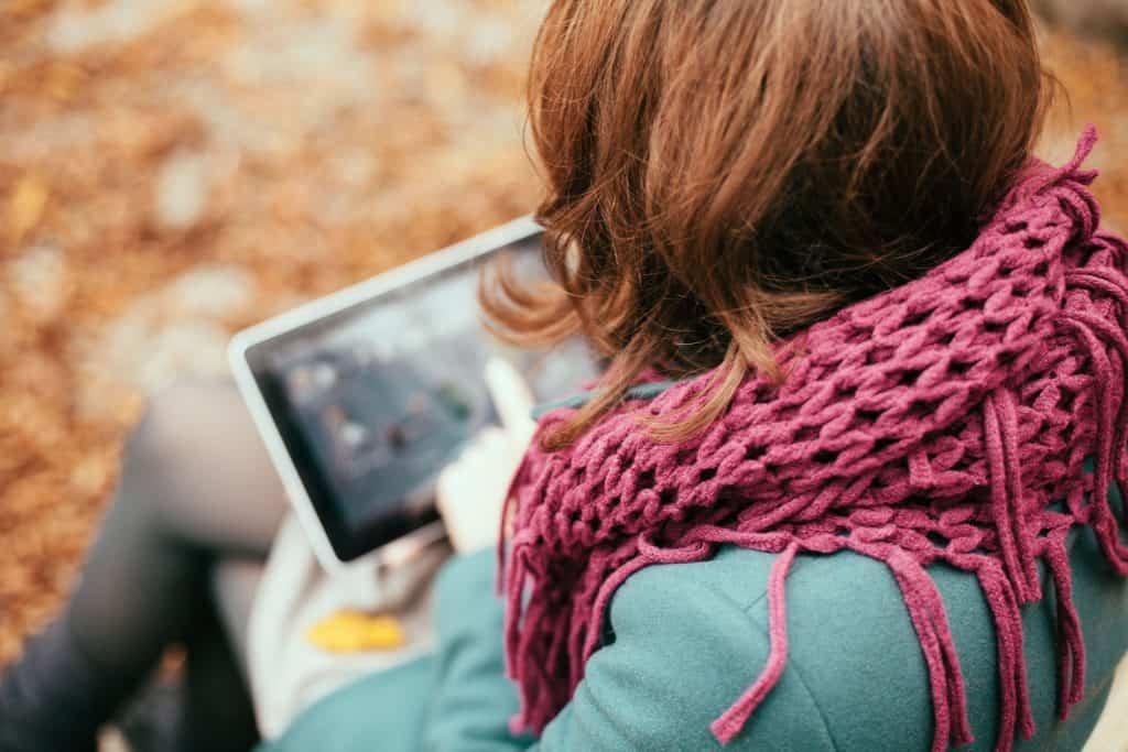 Na foto uma mulher vista de cima usando um notebook 2 em 1 em uma praça.
