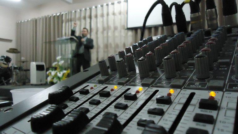 Imagem mostra uma mesa de som em uso em uma igreja.