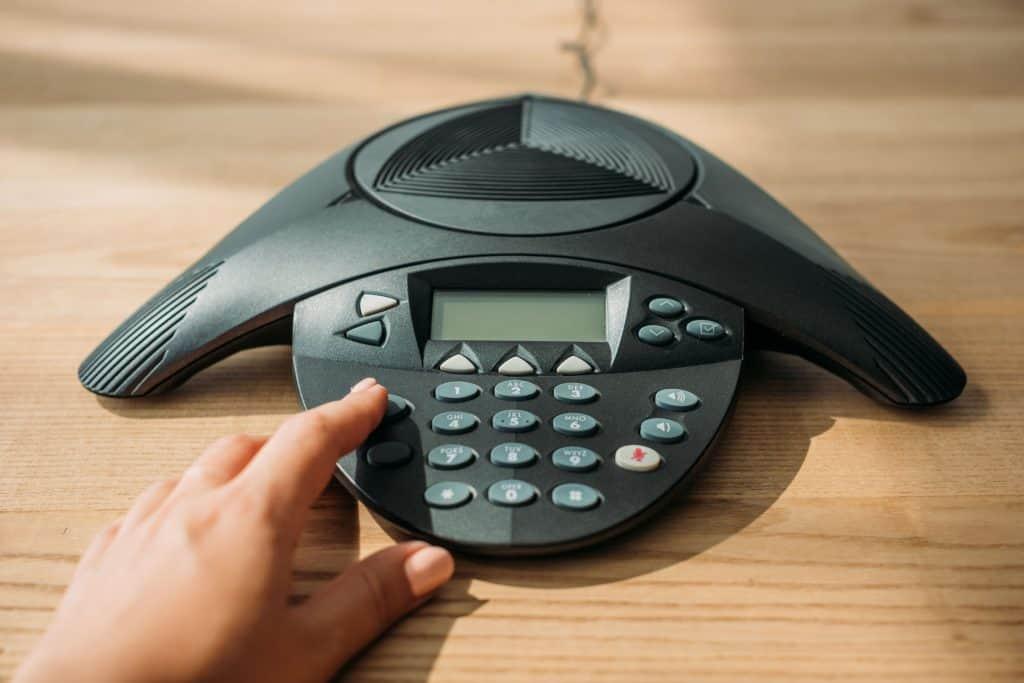 Na foto uma pessoa apertando um botão de um aparelho de audioconferência em cima de uma mesa de madeira.