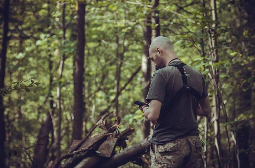 Imagem de um homem em meio à natureza consultando um smartphone.