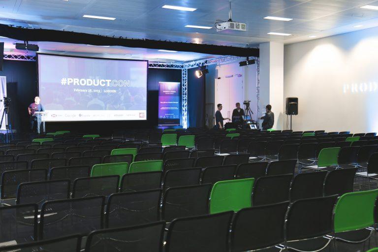 Imagem mostra uma sala com várias cadeiras, uma tela de projeção com uma apresentação e pessoas em volta