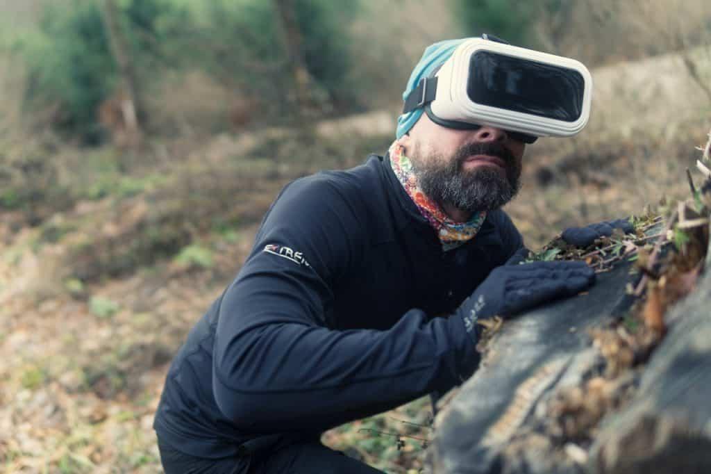 Homem vestido de preto, apoiado em uma pedra na natureza e utilizando o óculos de realidade virtual.