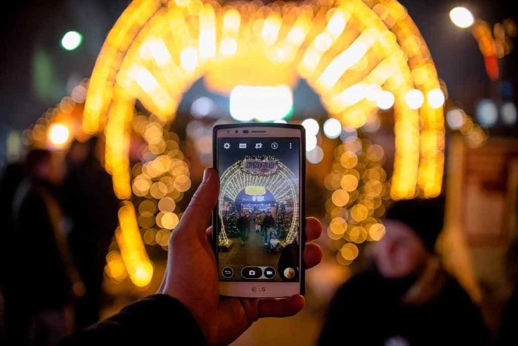 Mão segurando celular LG e tirando uma foto.