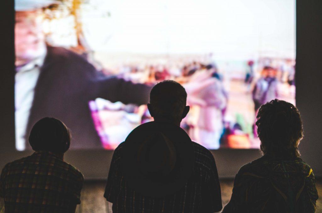 Imagem mostra três pessoas em pé em frente a um enorme aparelho de televisão.