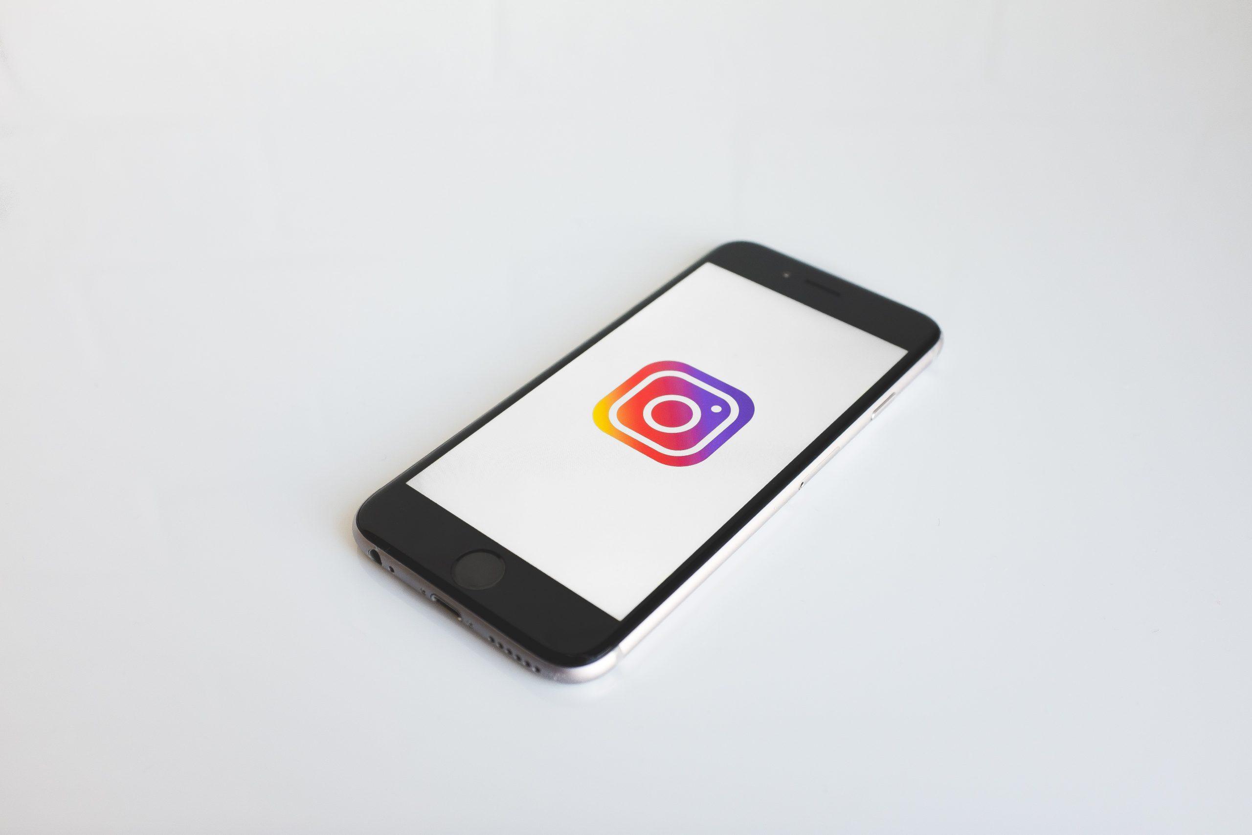 Celular em um fundo branco com a logo do instagram