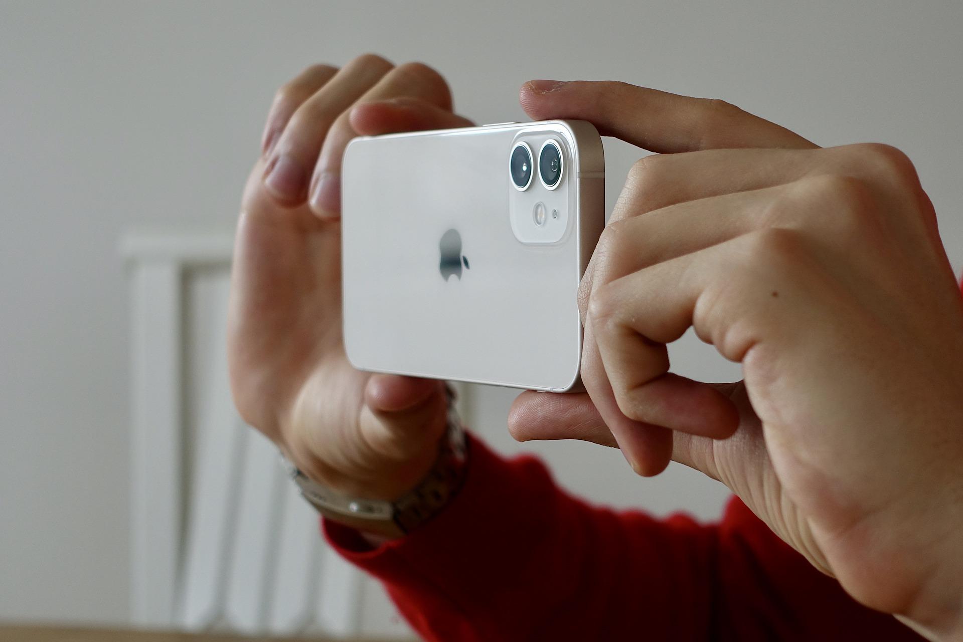 Destaque de mão tirando foto com celular.