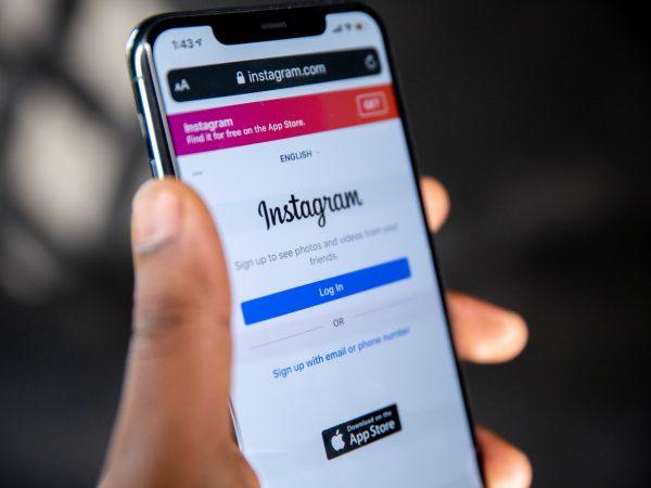 Na foto uma pessoa segurando um celular na mão com a tela de login de Instagram aberta.